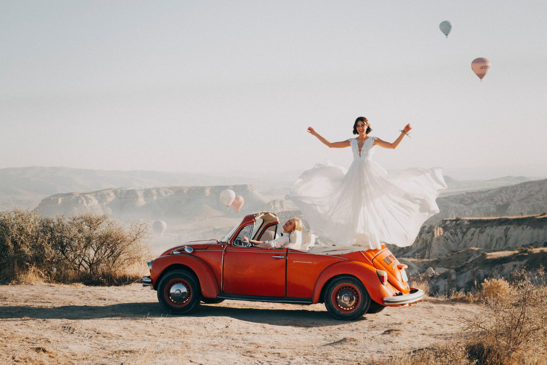 woman standing on volkswagen beetle