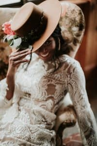 woman in white lace long sleeve dress wearing a hat