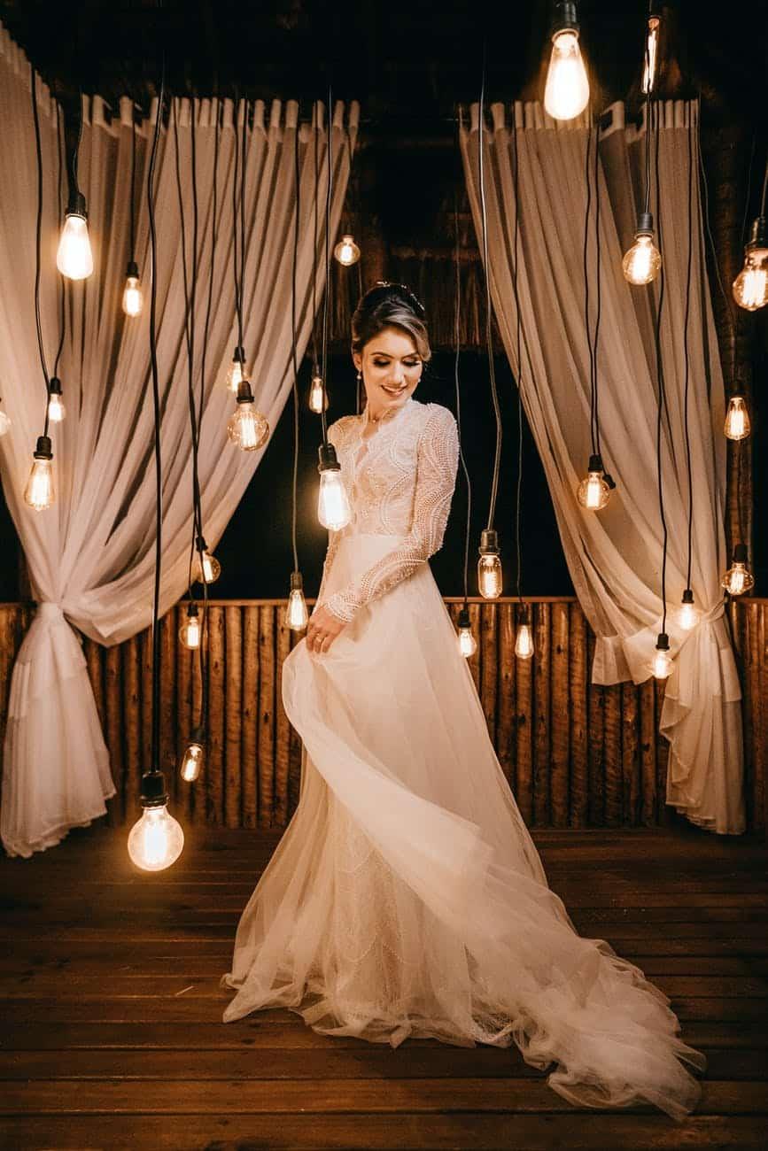 woman standing beside hanging light bulbs