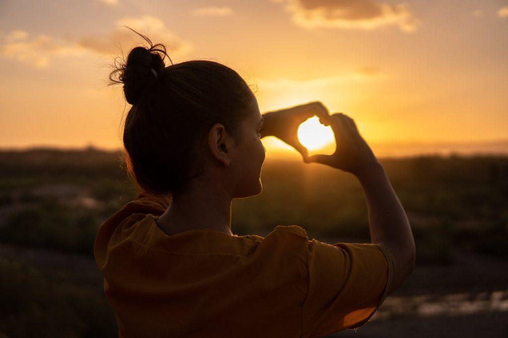 woman doing hand heart sign