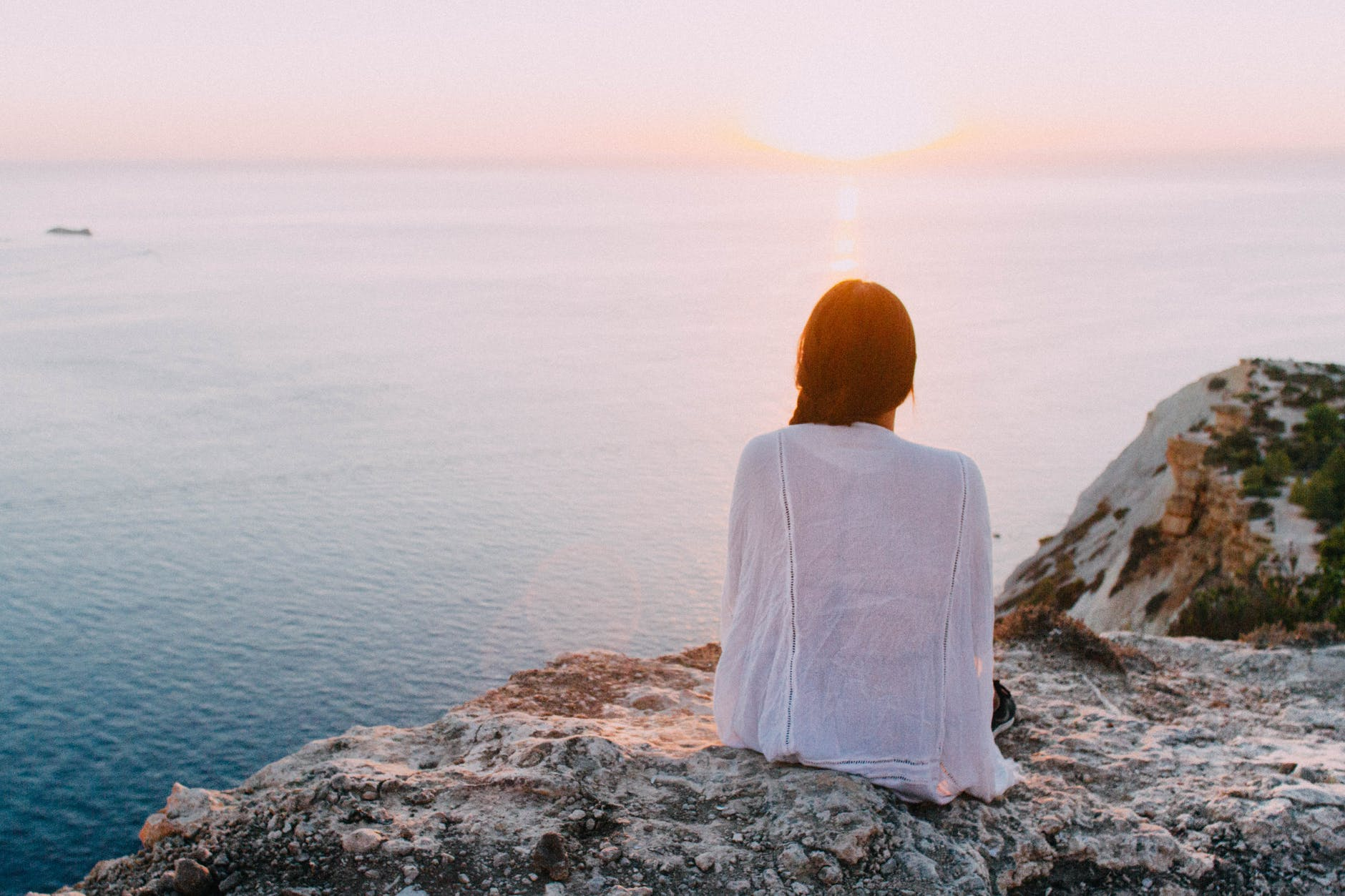 woman sitting on gray rock near body of water