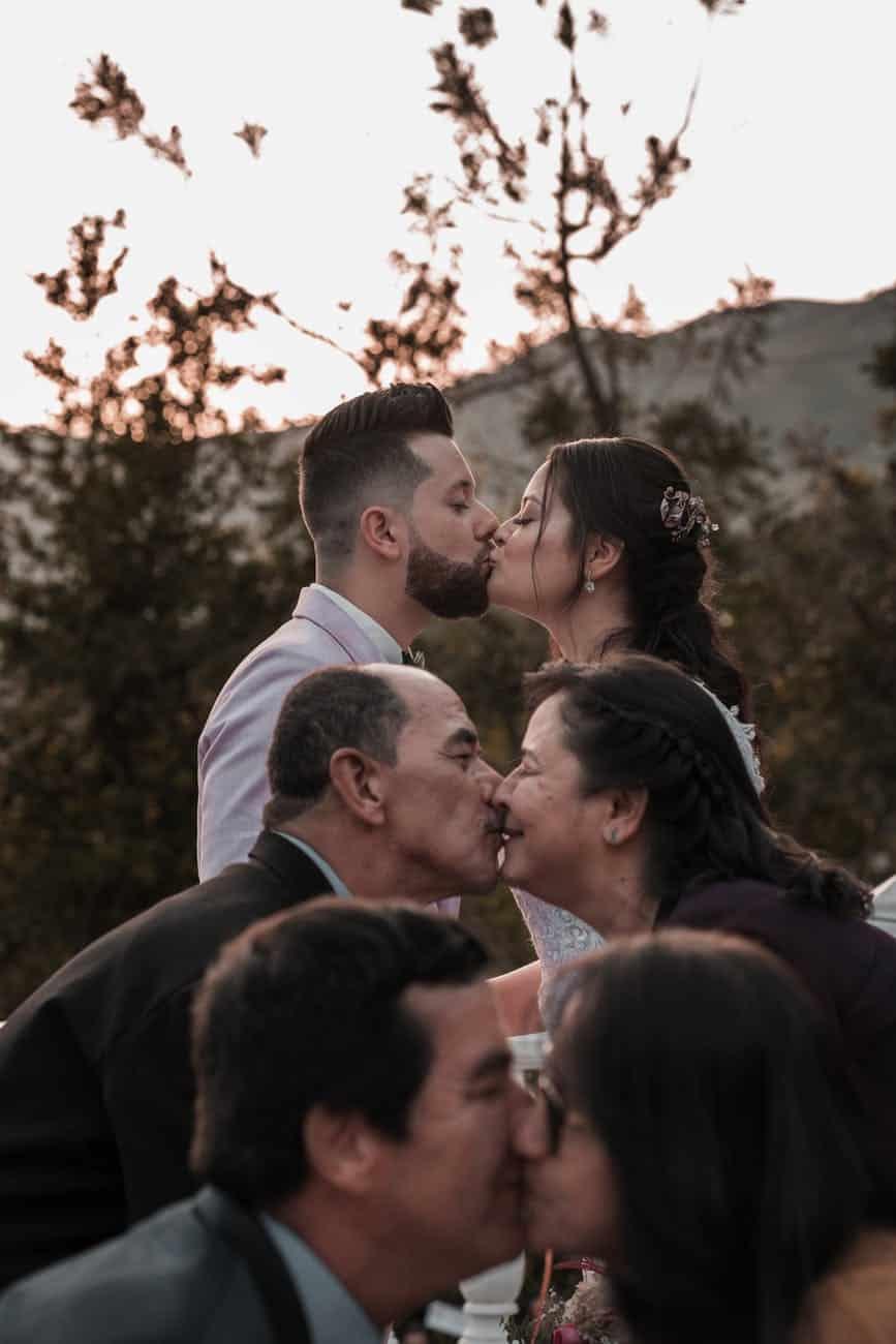 elegant ethnic newlyweds and parents kissing on wedding day outdoors