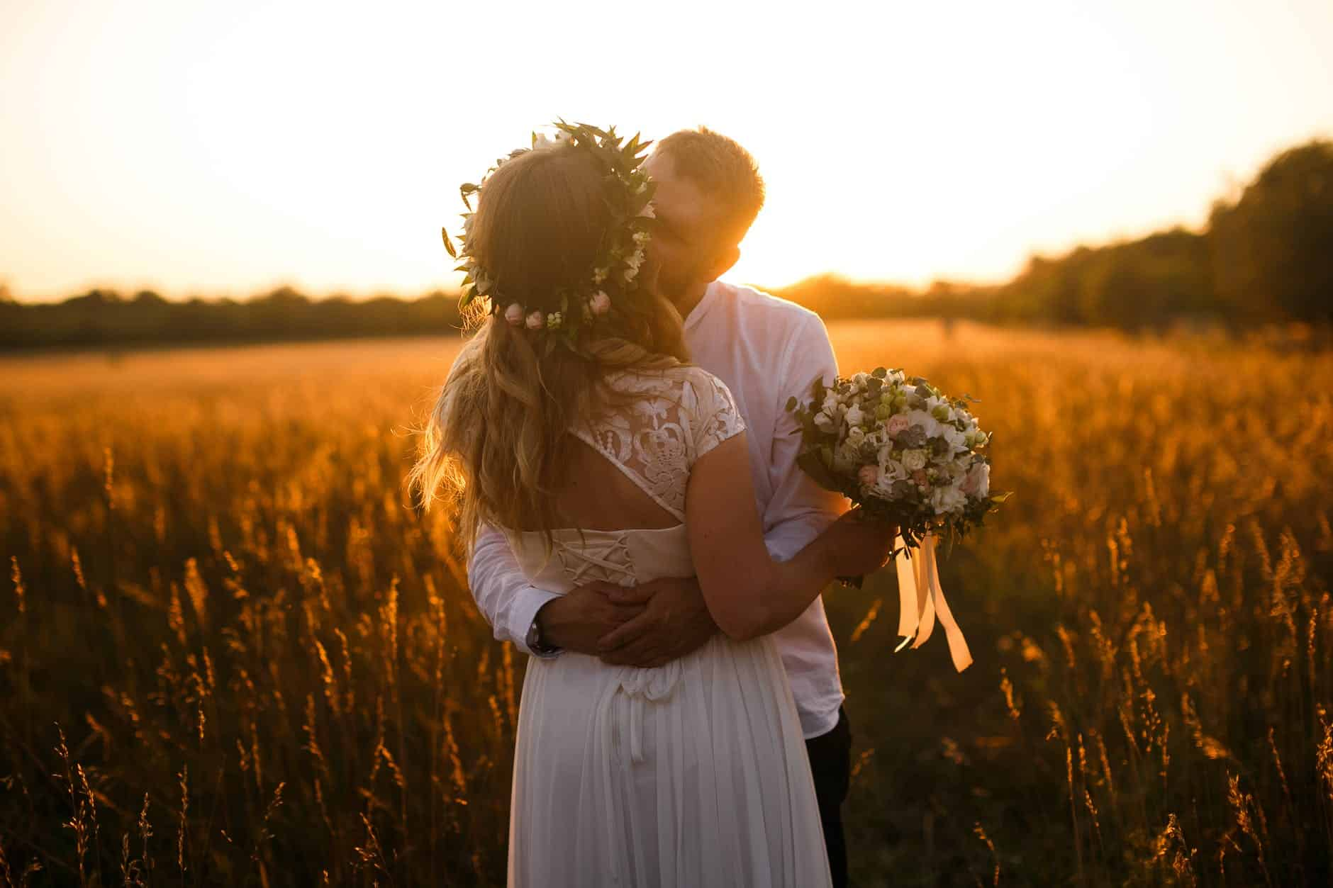 man and woman standing in front of brown grass field kissing each other