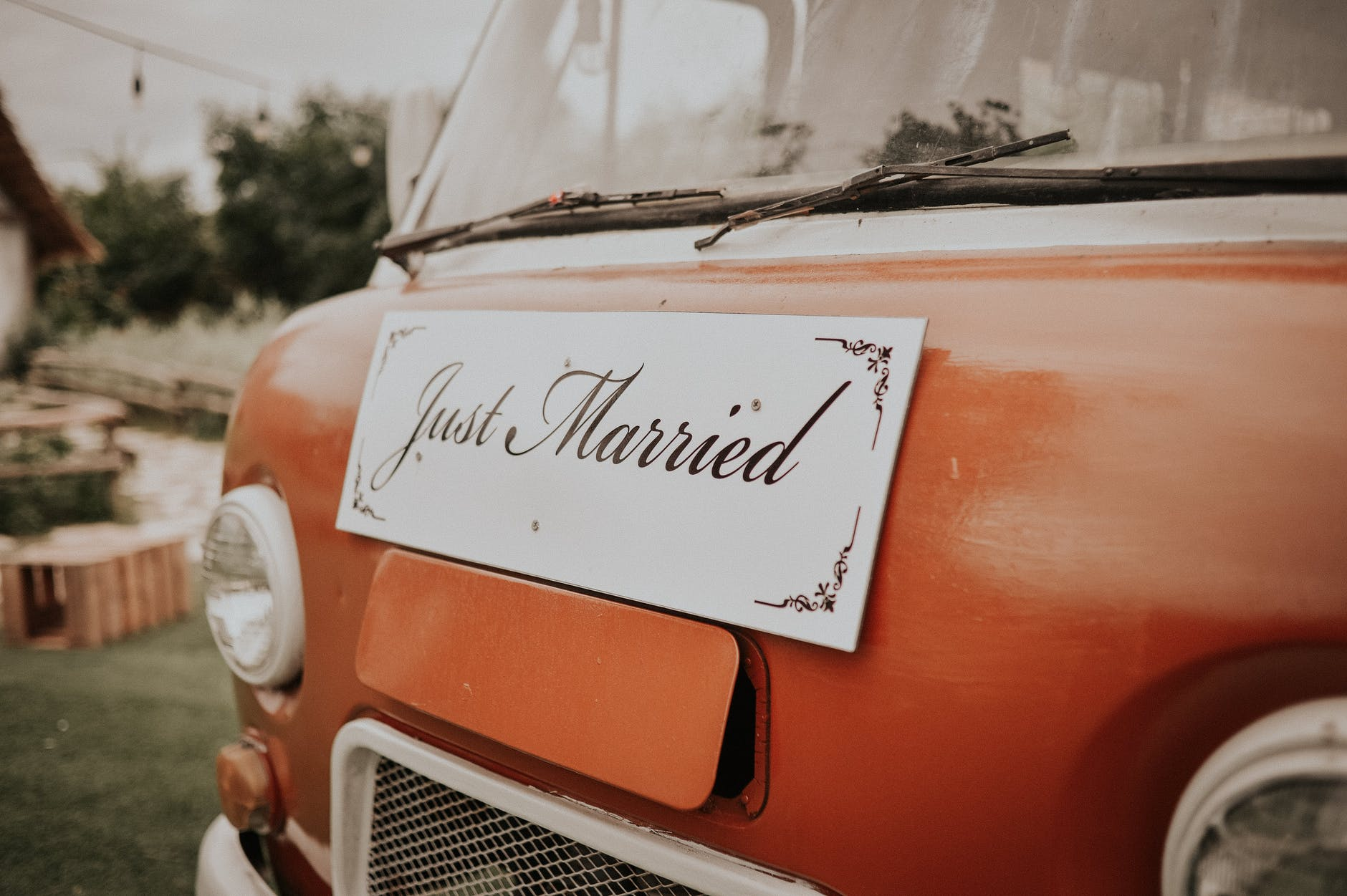 just married plank board in front of red van