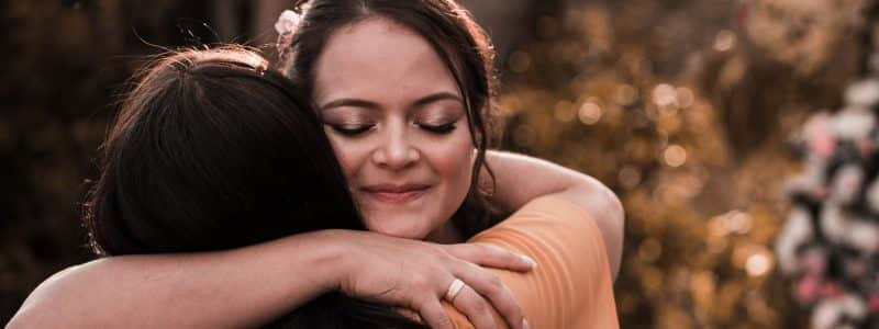 content ethnic woman embracing unrecognizable girlfriend in daylight