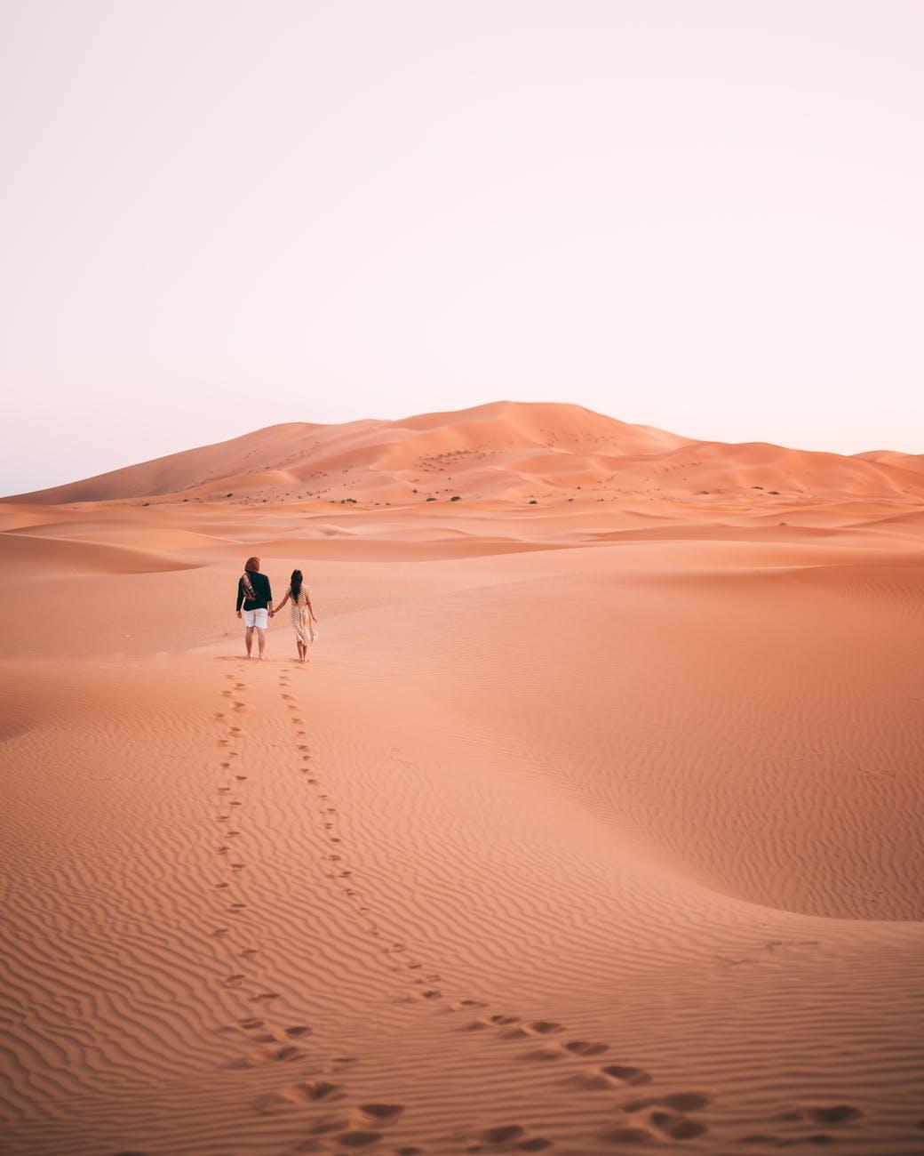photo of people walking on dessert