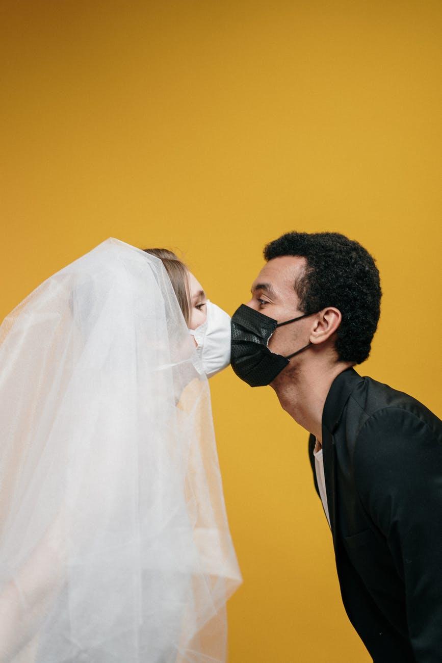 man in black suit kissing woman in white veil