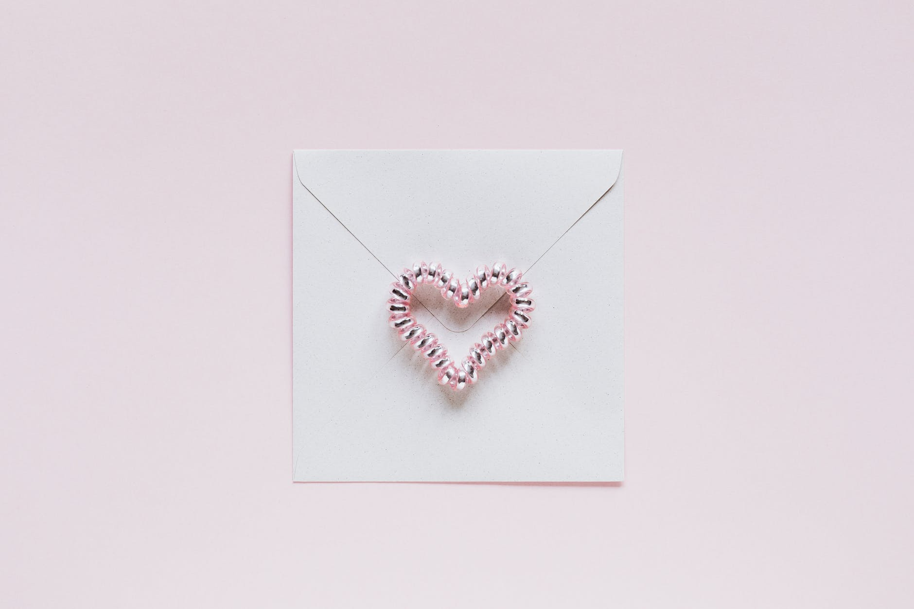 envelope with handmade bead heart on san valentines day