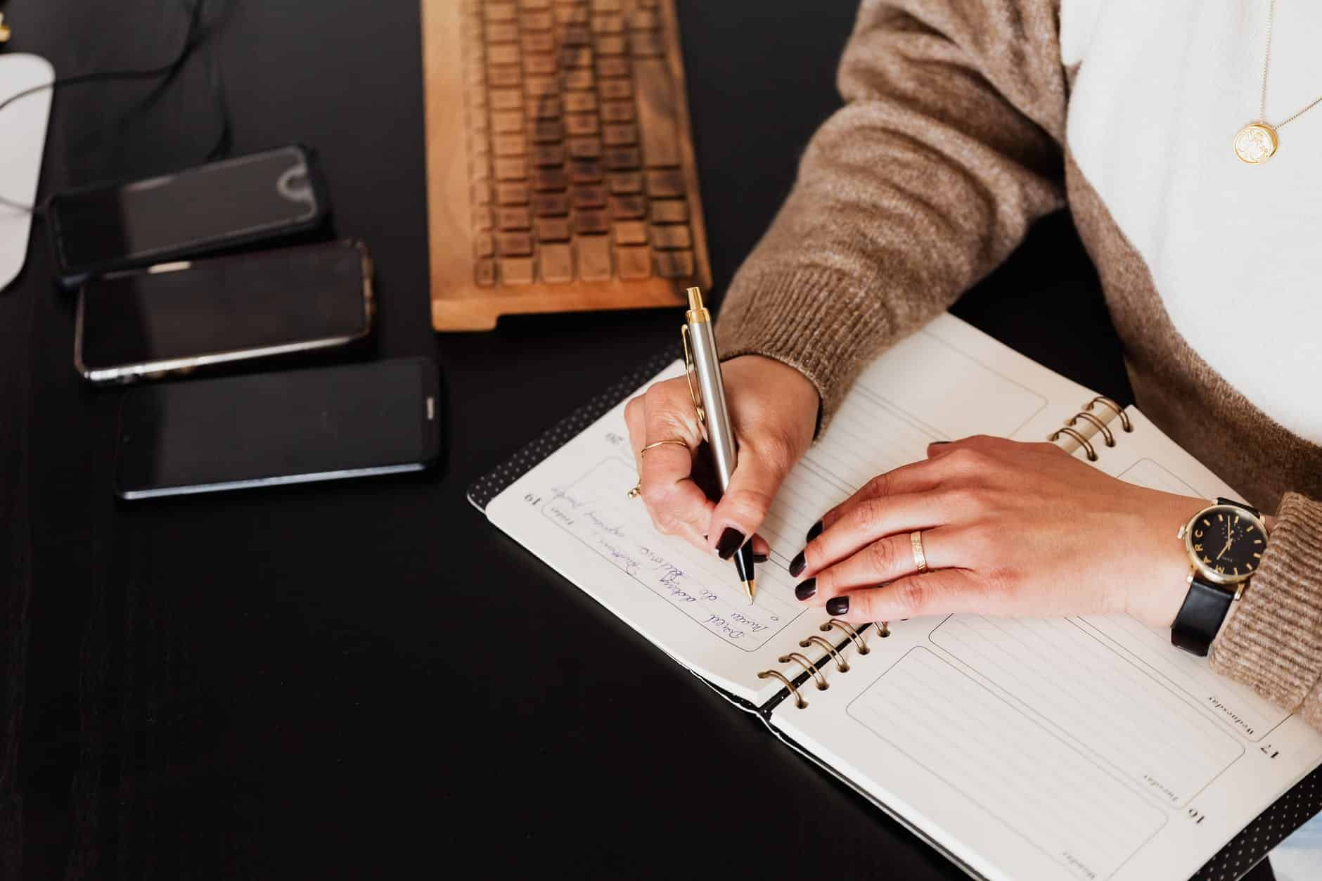 crop stylish woman writing in notebook