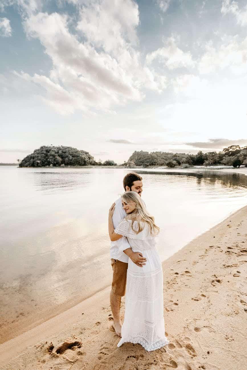 happy couple embracing on sandy sea shore during honeymoon