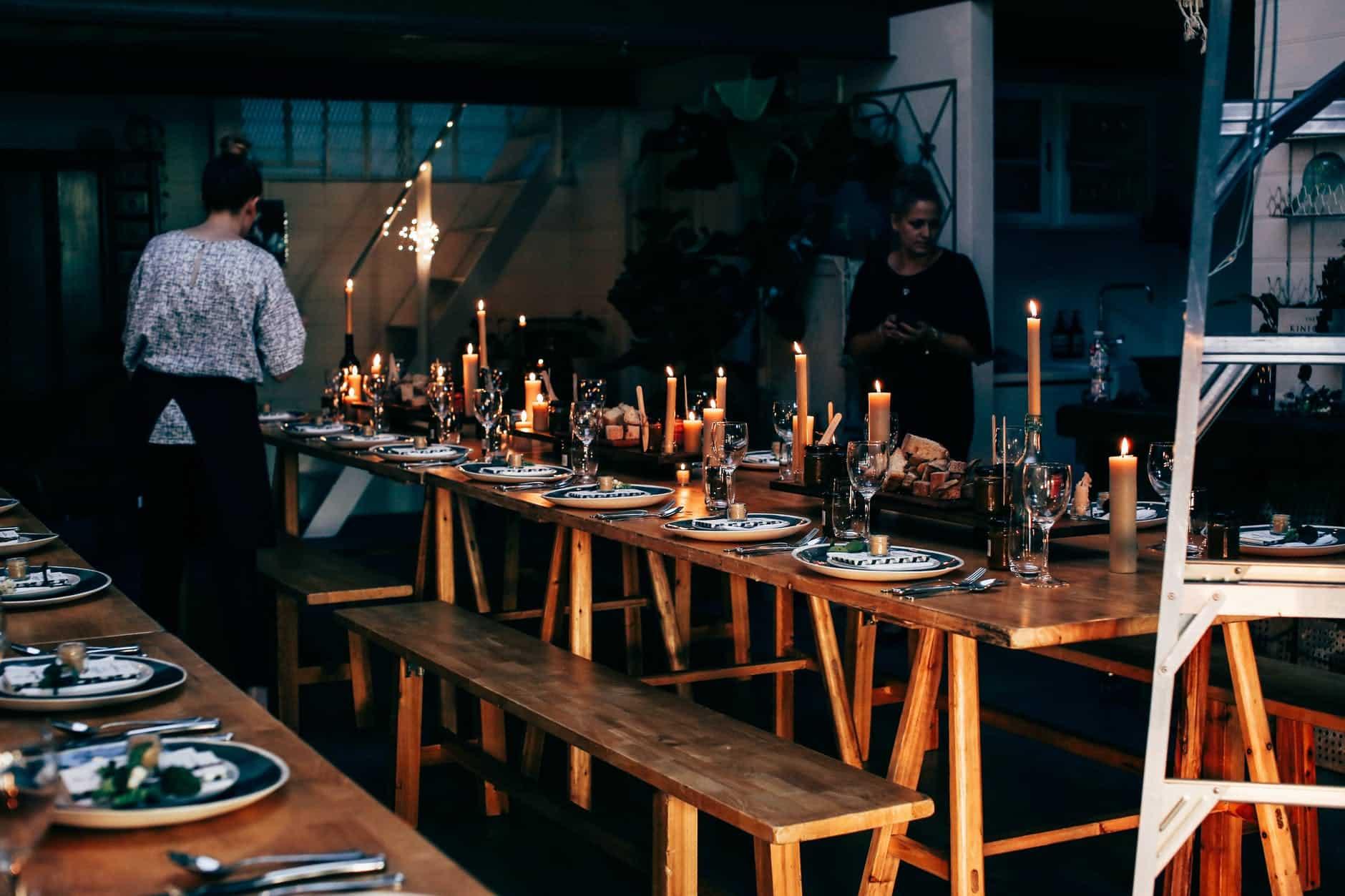 unrecognizable women preparing banquet in modern apartment