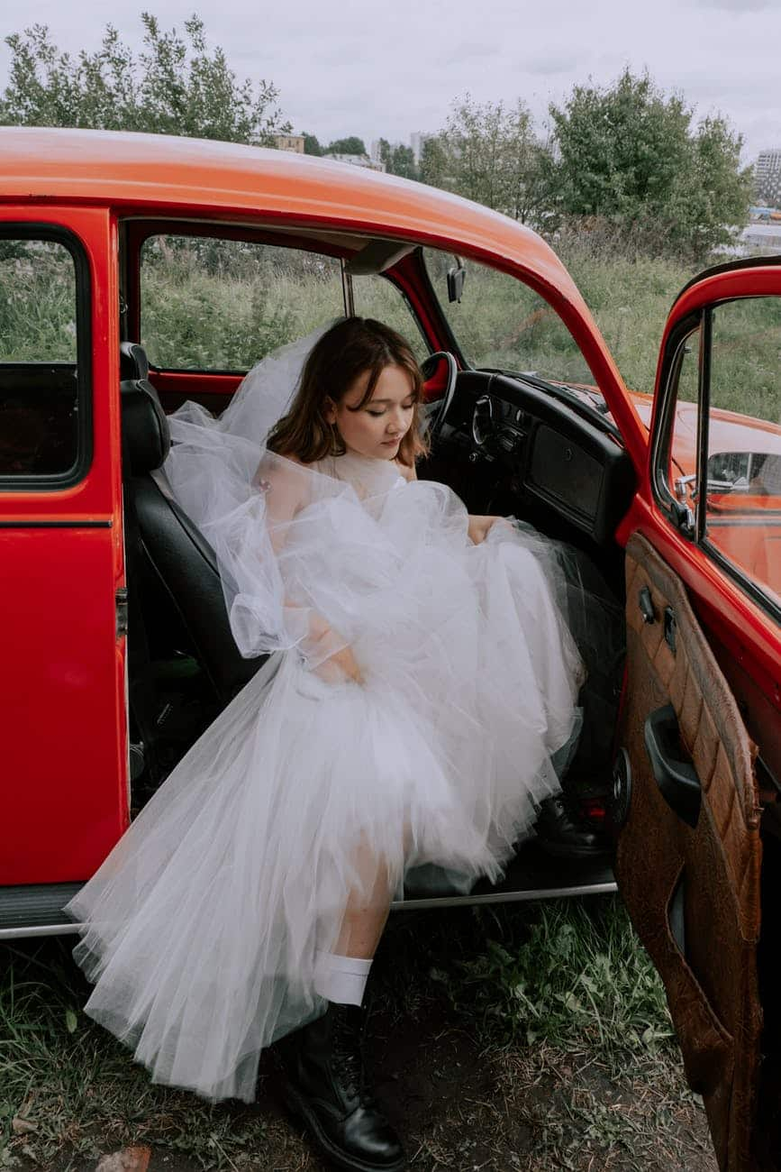 woman in white dress sitting on red car