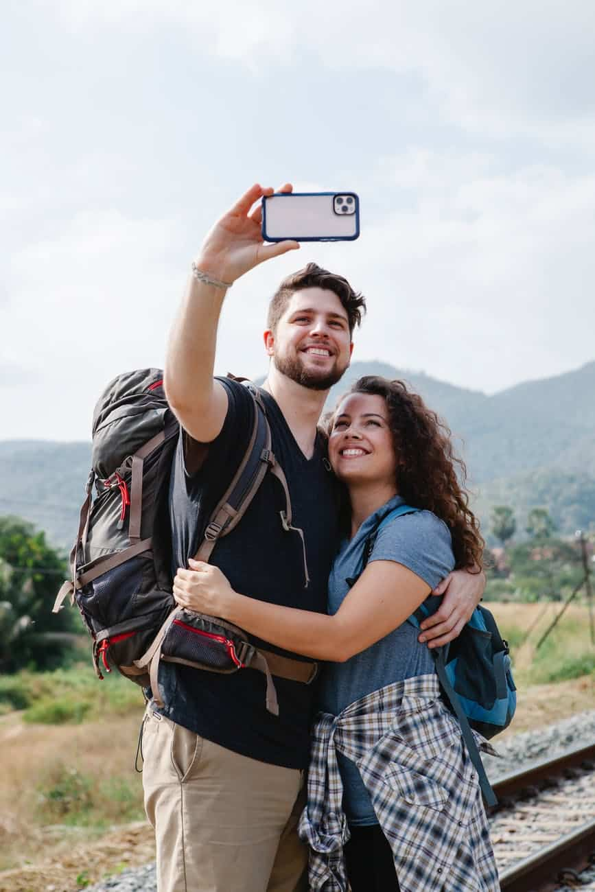 couple of travelers taking selfie on smartphone near grassy valley