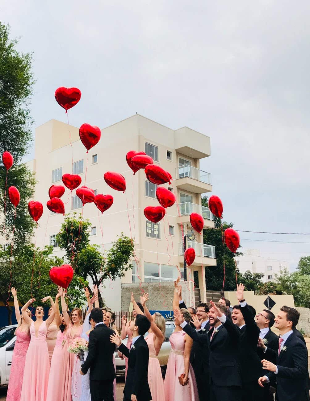 women wearing pink dresses and men wearing black suit jacket and pants raising hands with red heart balloons