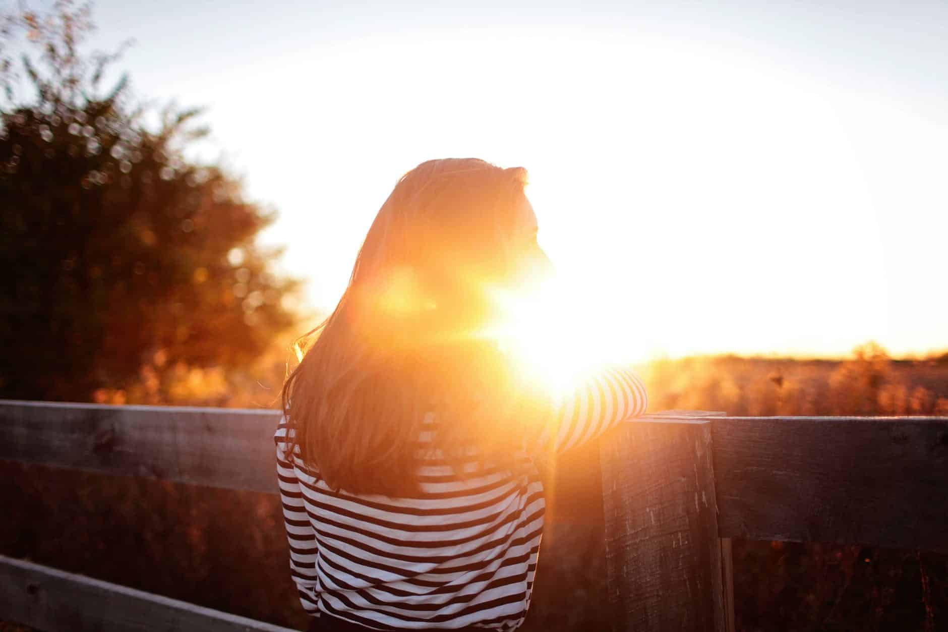 rear view of woman standing in balcony during sunset