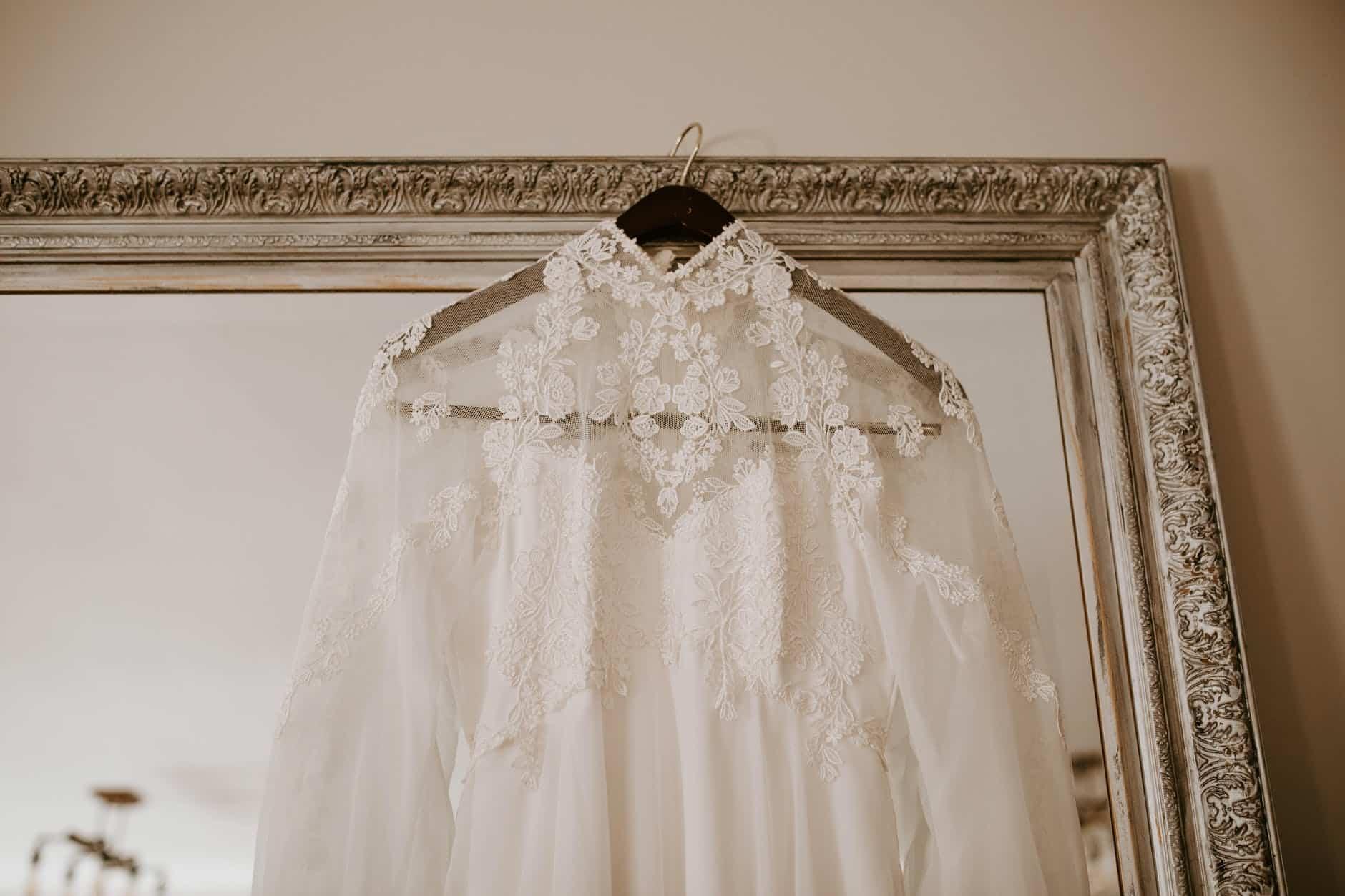 elegant bridal dress hanging on mirror