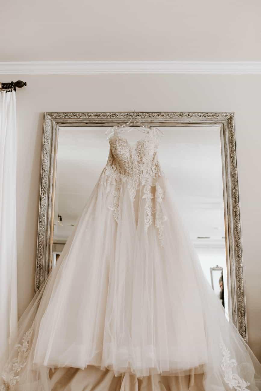 stylish white bridal dress hanging on wall with mirror before wedding celebration