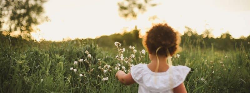 girl standing beside white flower field