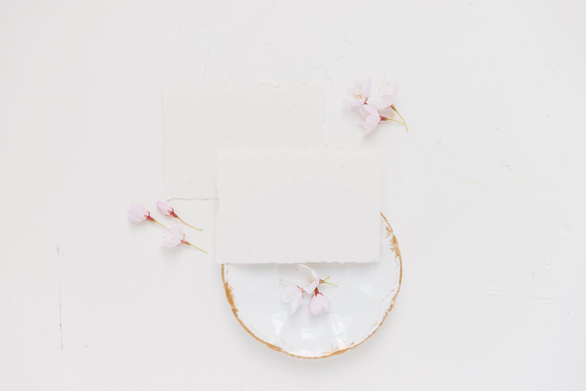 white paper on white floral textile
