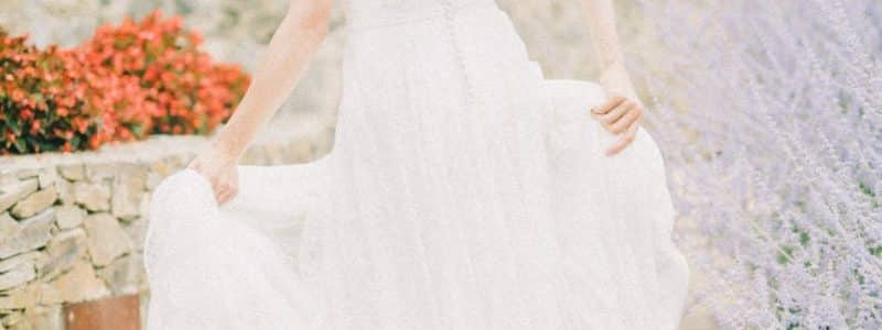 woman in white wedding dress smiling while looking back