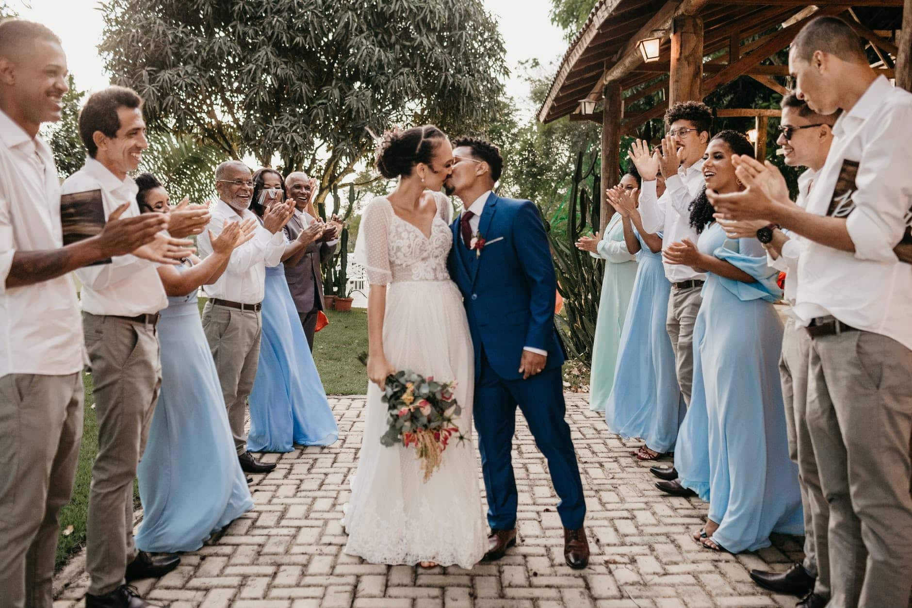 multiethnic couple kissing between smiling guests on wedding day