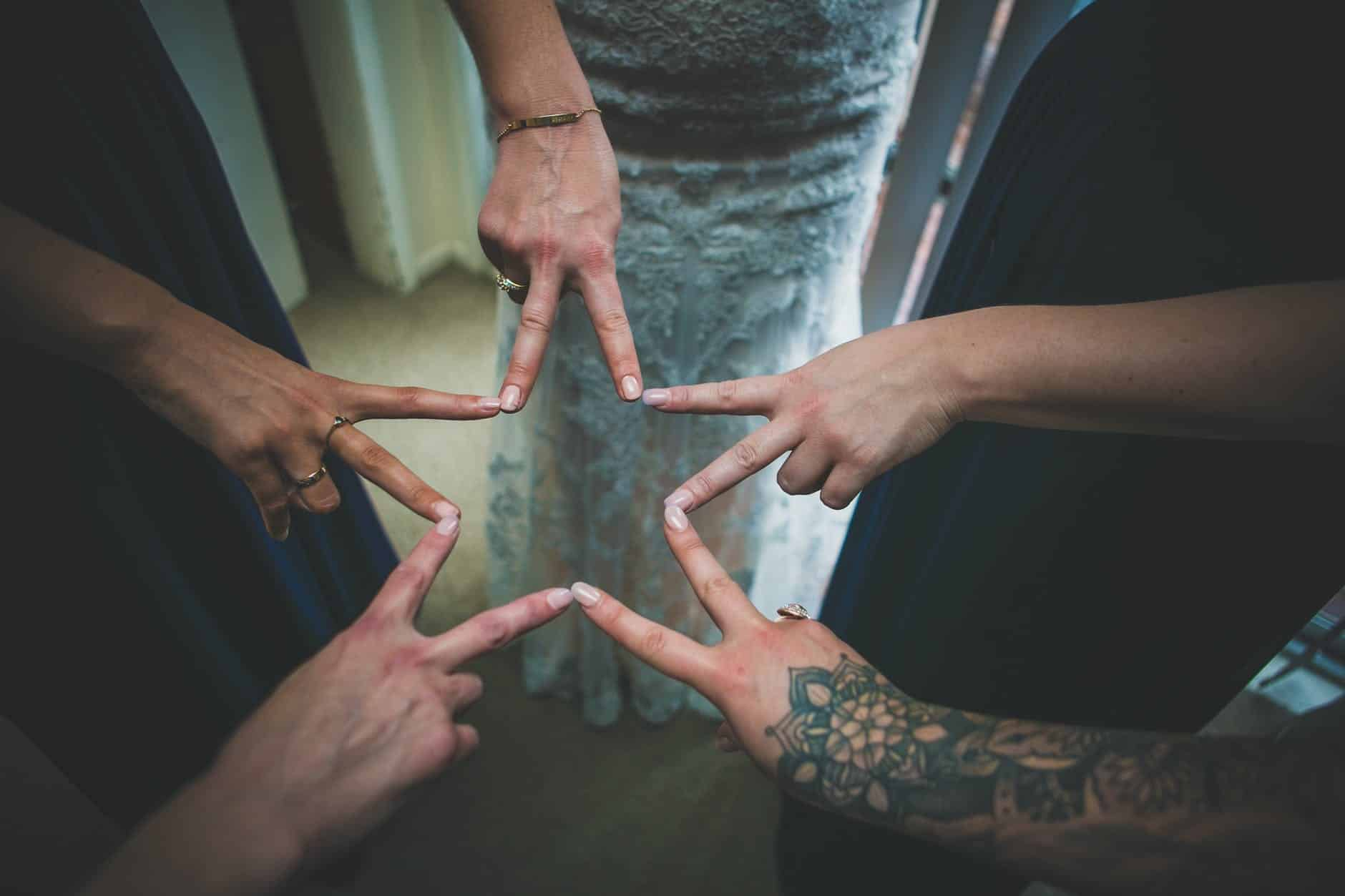 anonymous bride and bridesmaids showing v sign on wedding day