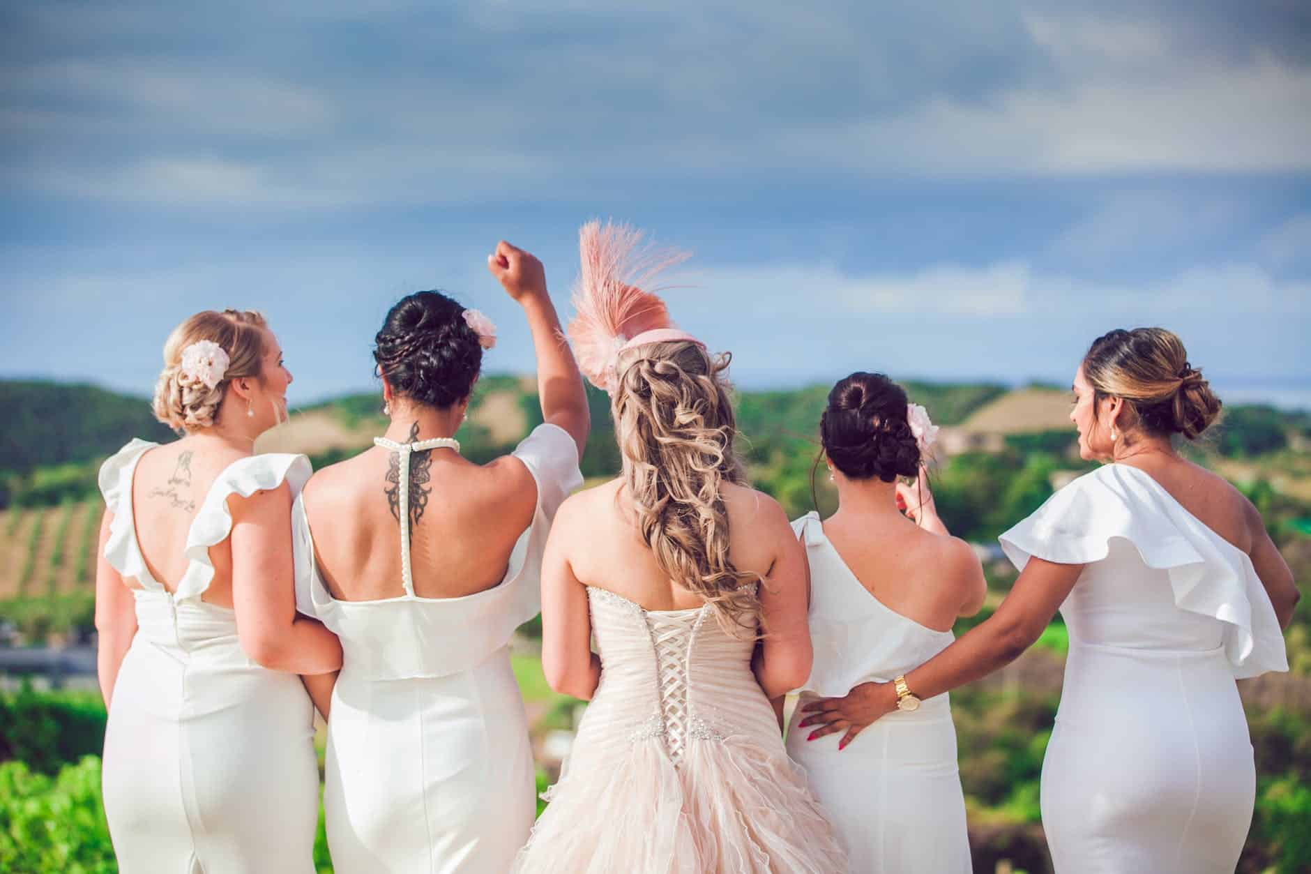 anonymous bridesmaids and bride on hill near plants and trees