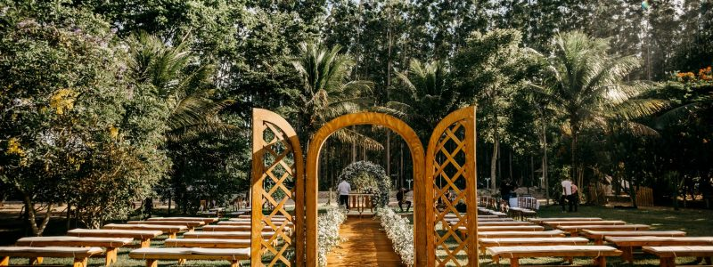 wedding arch and guest benches placed in verdant park
