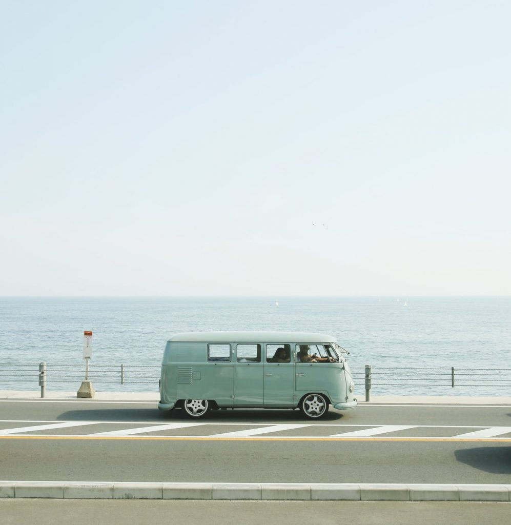 van parked beside the road near handrail and ocean