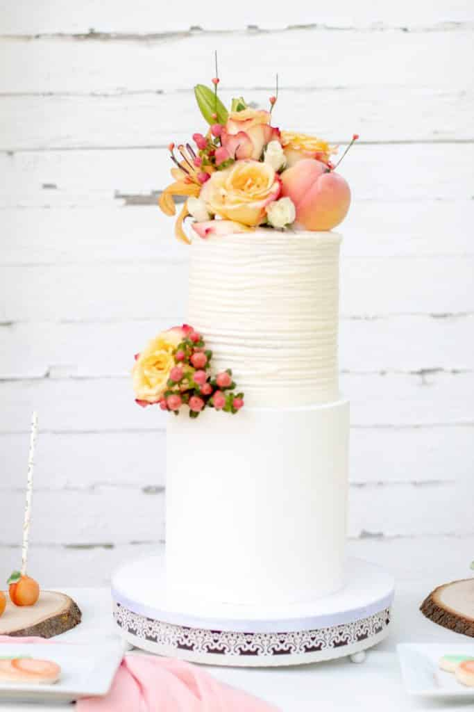shallow focus photo of yellow and pink flowers on two tier cake