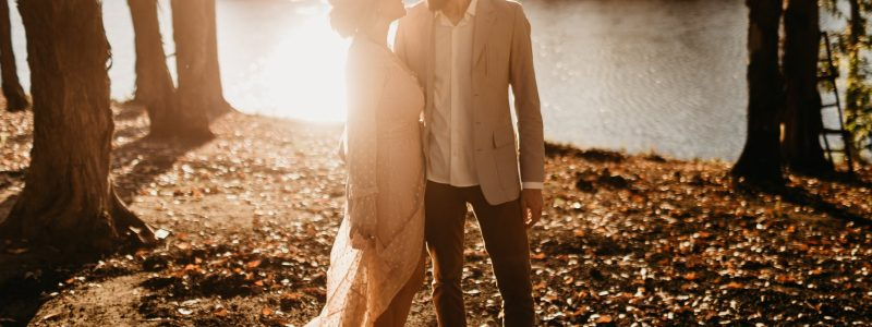 man and woman standing near lake