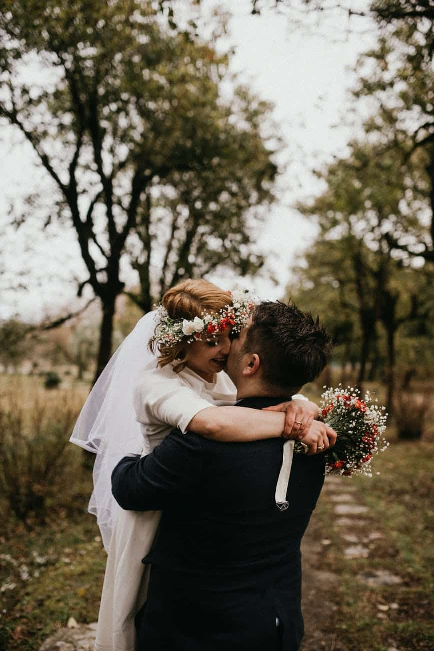 man in black suit with woman wearing white dress kissing woman