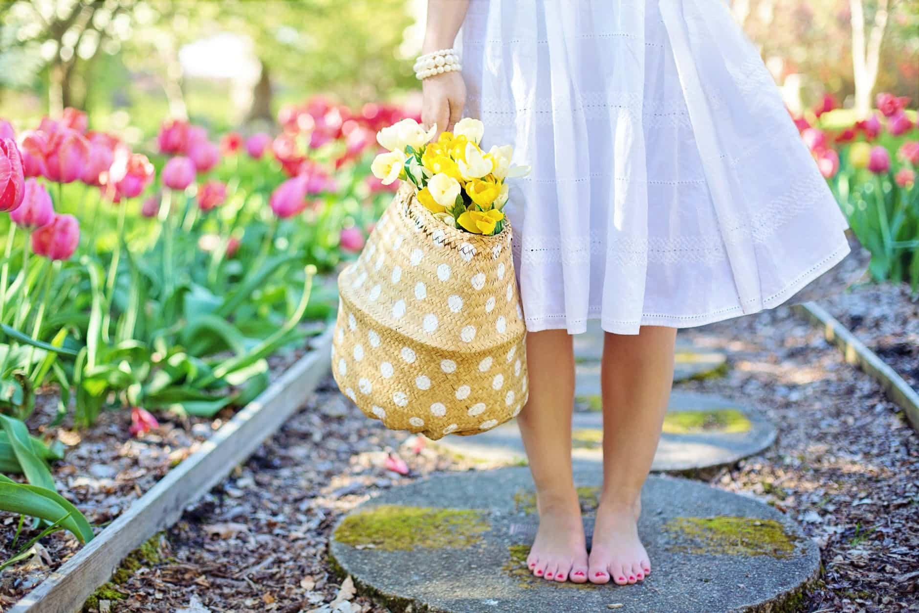 woman holding brown basket with yellow flowers
