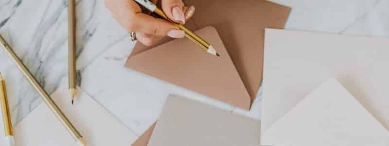 person holding a pencil and writing on an envelope