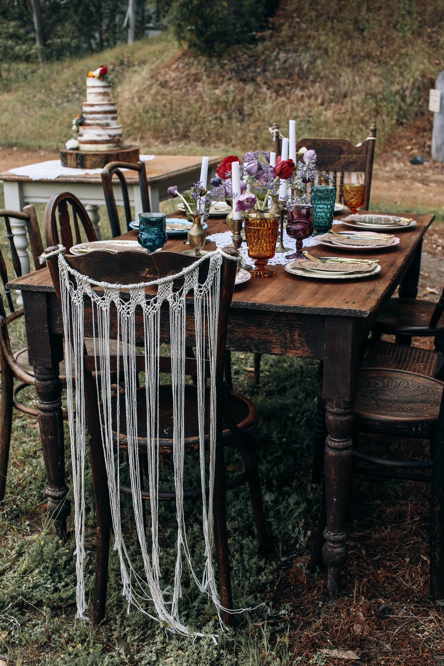 festive wooden table and chairs placed in nature in daytime