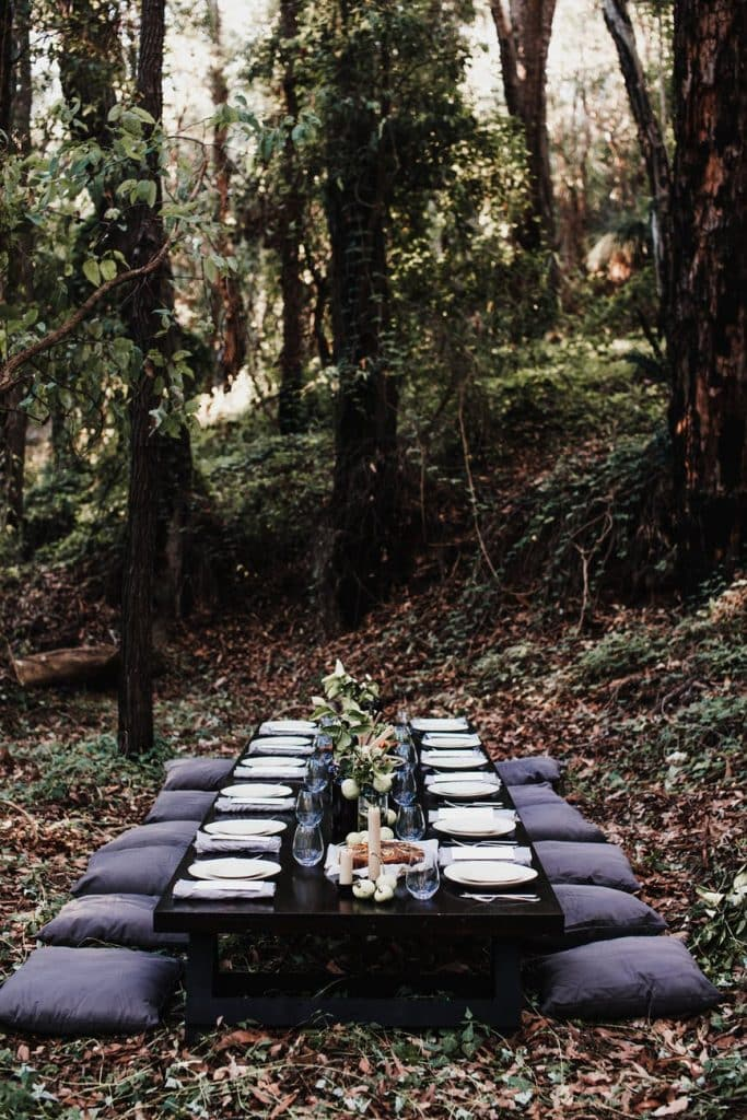 table set on lawn in forest