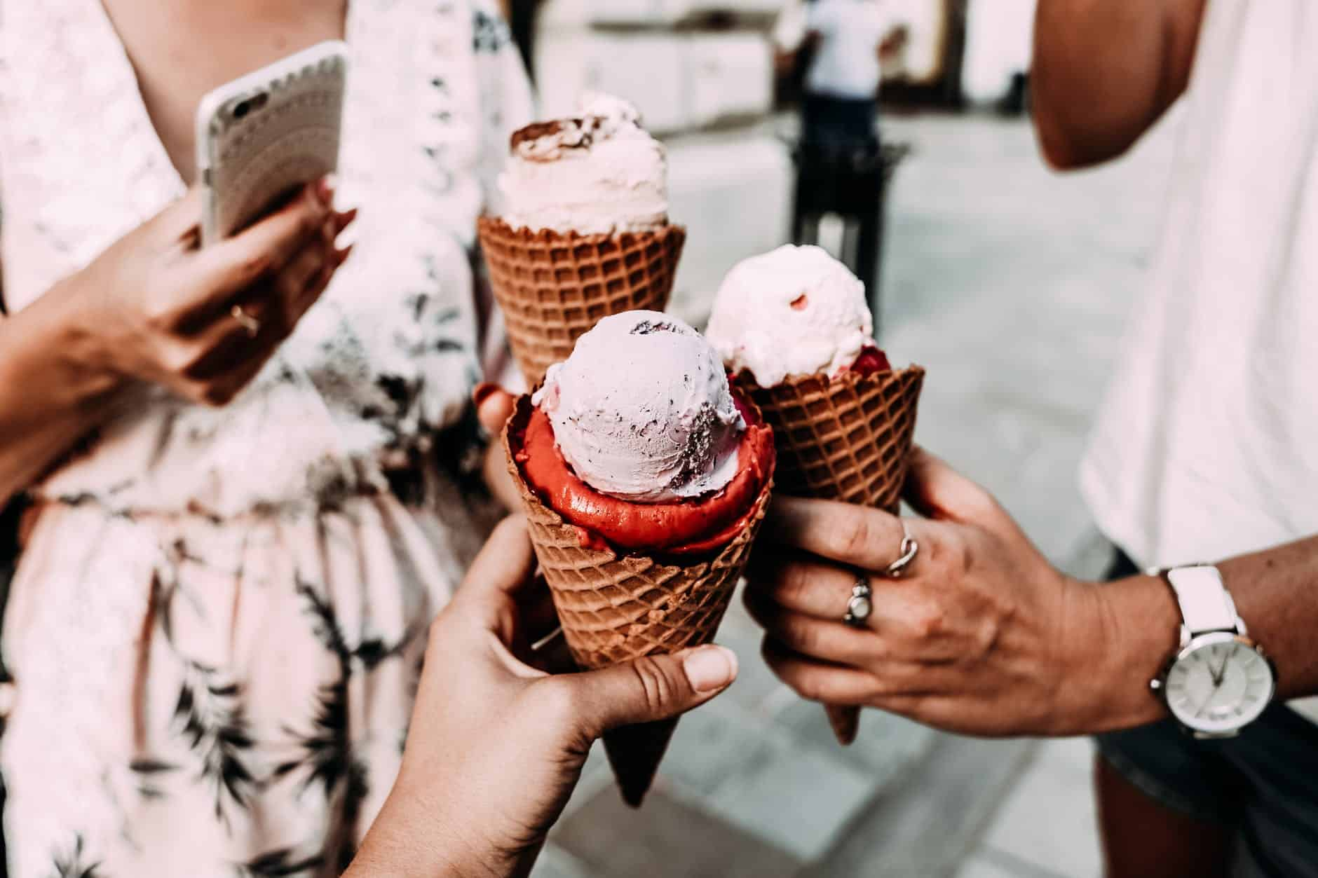 crop unrecognizable friends clinking ice creams on street