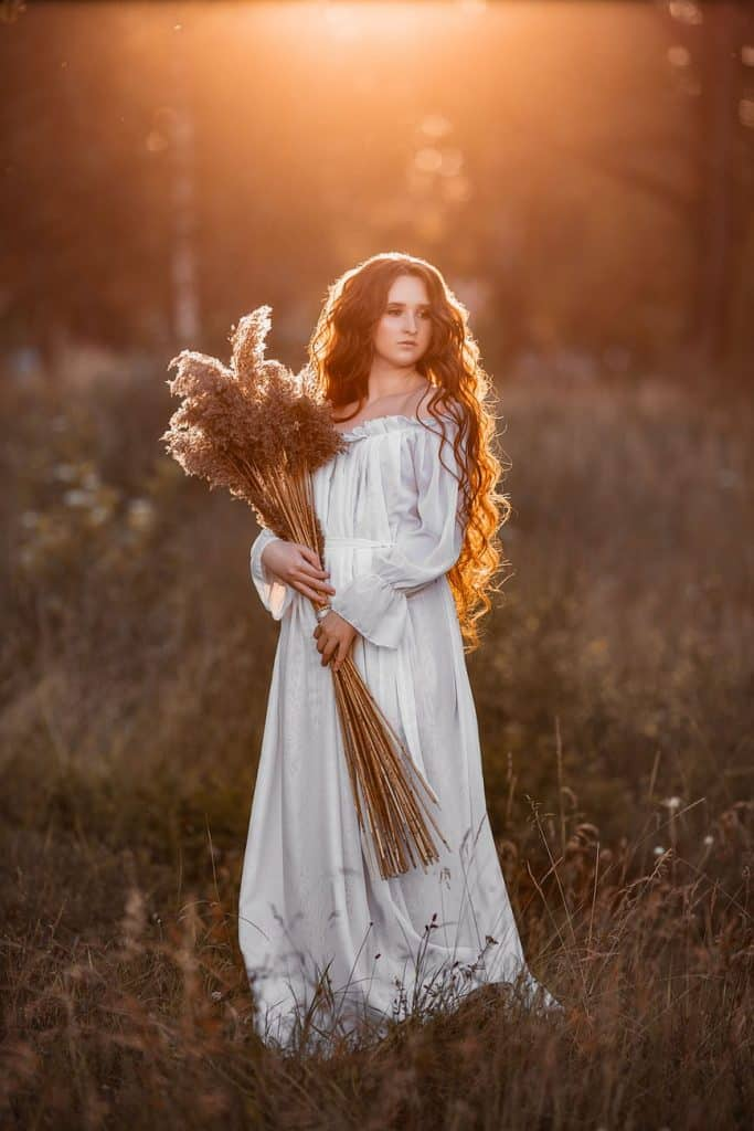 woman with flowers in field at sunset