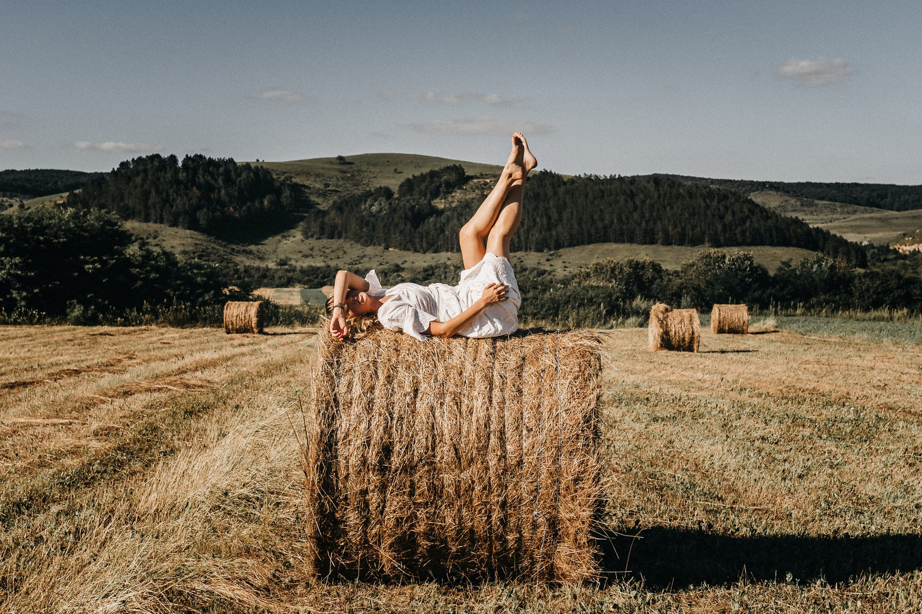 woman resting on haystack in countryside
