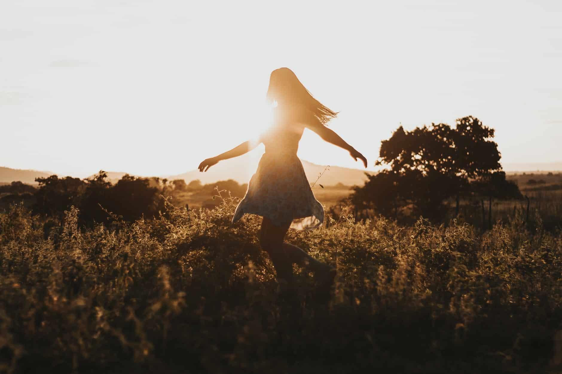 woman turning around on green fields