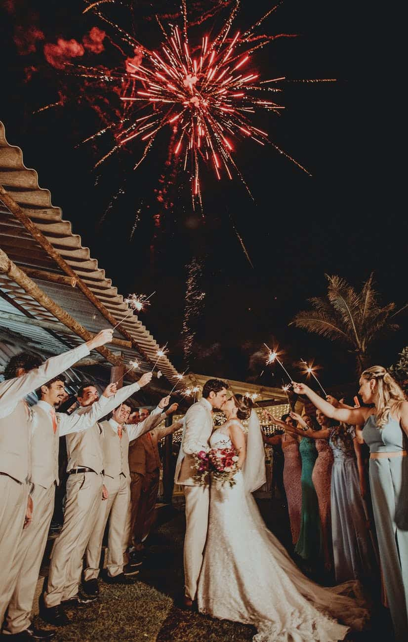 red fireworks above wedding couple