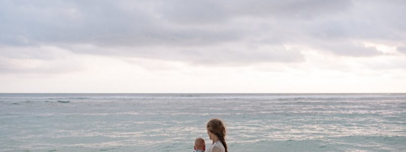 photo of woman carrying baby