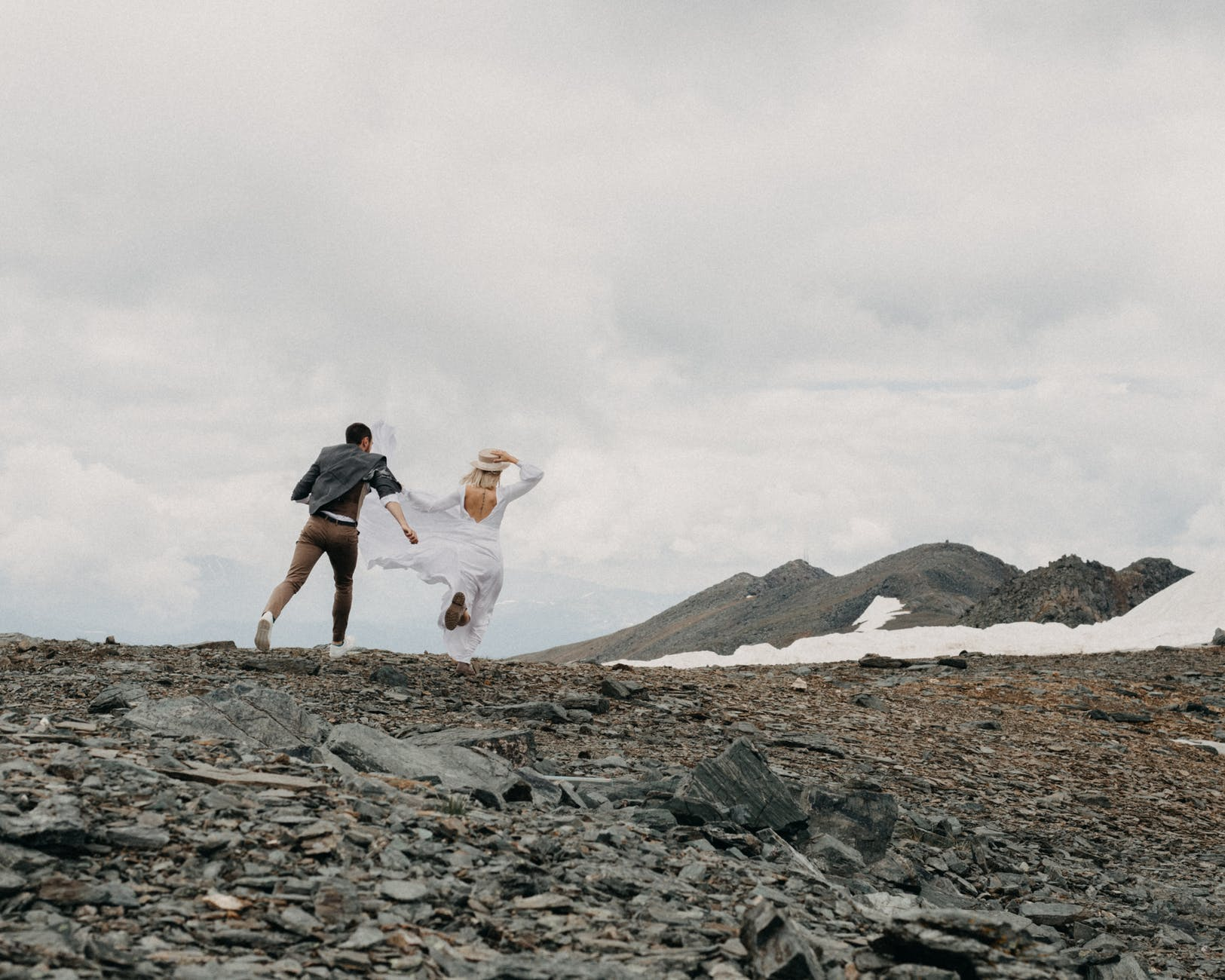 faceless newlywed couple running on mount under cloudy sky