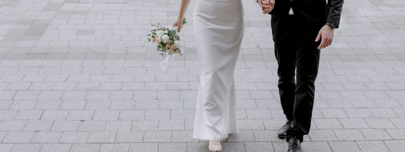 man in black suit holding hand of woman in white wedding dress